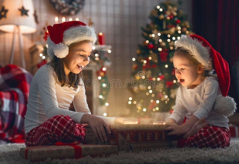 Enfants ouvrant des cadeaux de Noël photographie stock libre de droits