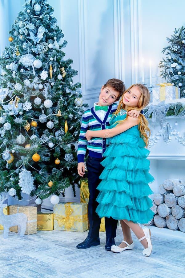 Enfants par un arbre de Noël photos stock
