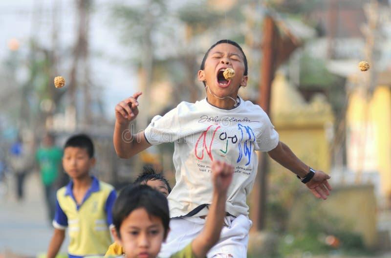 Enfants participant à la 'morsure les biscuits accrochants' photographie stock