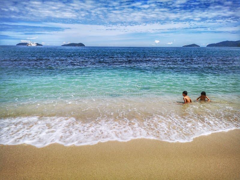 Enfants passant le temps dans la plage heureusement image libre de droits