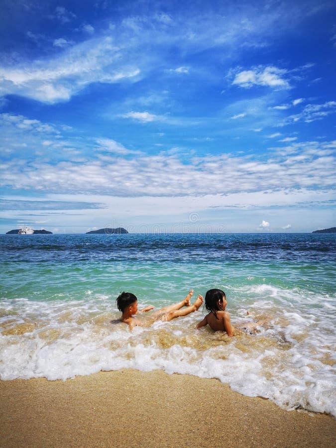 Enfants passant le temps dans la plage heureusement images libres de droits