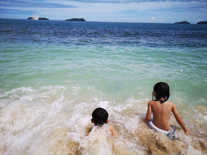 Enfants passant le temps dans la plage heureusement images stock