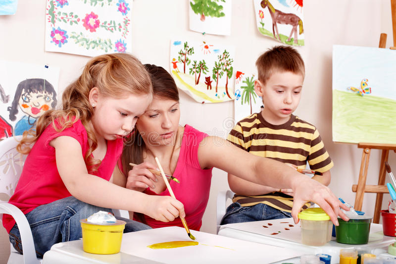 Enfants peignant avec le jeune femme. image libre de droits
