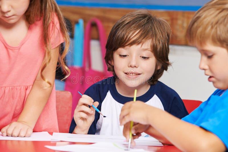 Enfants peignant dans la classe d'art à l'école images libres de droits