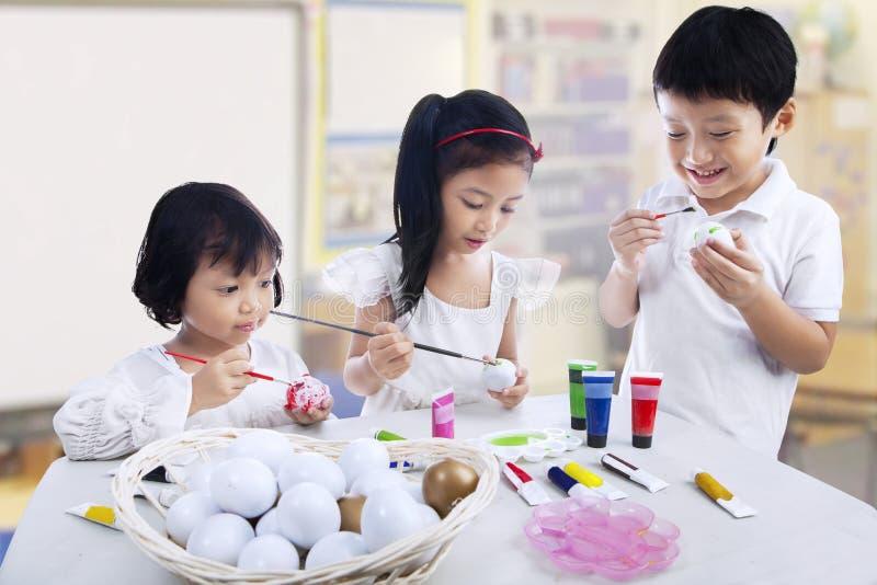 Enfants peignant des oeufs images stock