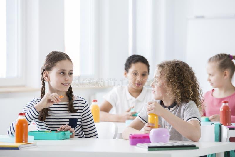 Enfants pendant le temps de casse-croûte dans leur salle de classe Bouteilles de fruit images libres de droits