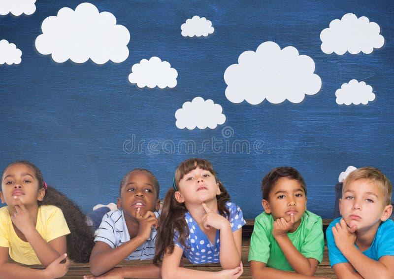 Enfants pensant et mur bleu avec des nuages photographie stock libre de droits