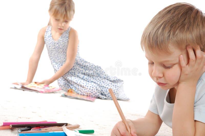 Enfants pensifs dessinant le relevé et l'écriture photo libre de droits