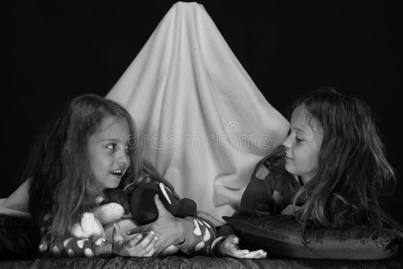 Enfants portant les jammies rouges dans le lit sur le fond noir Amis ayant l'amusement avec des ours de nounours dans la tente co photographie stock libre de droits