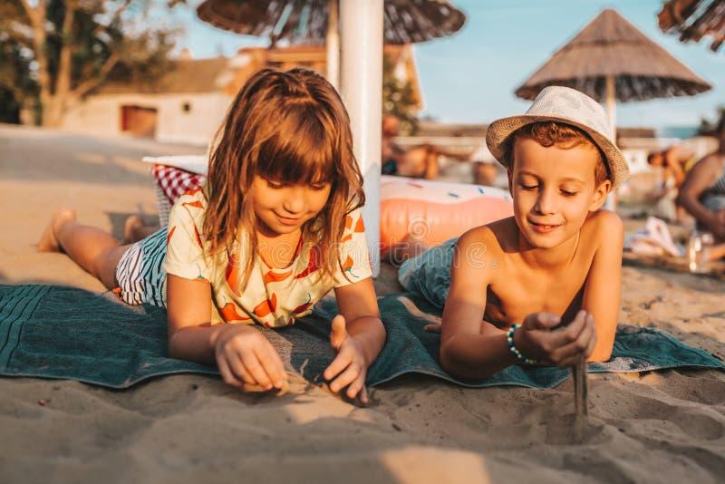 Enfants positifs heureux jouant avec le sable sur la plage photographie stock