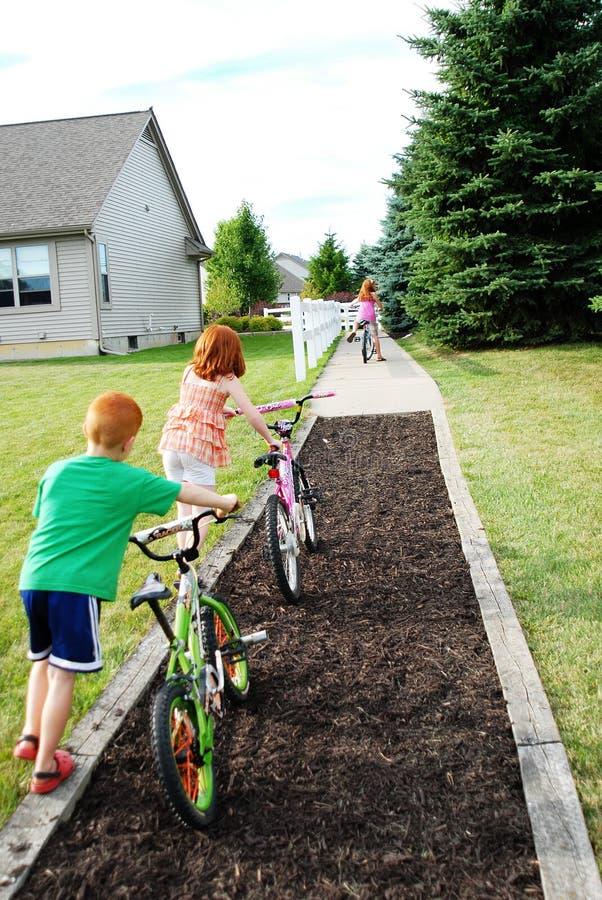Enfants poussant des vélos sur le chemin image libre de droits
