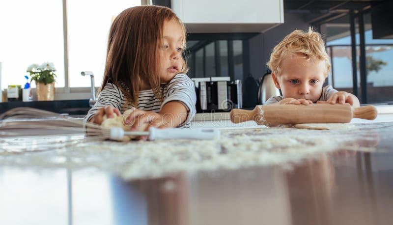 Enfants préparant des biscuits dans la cuisine photographie stock