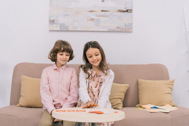 enfants préparant la salutation pour le jour de mères à la maison photo libre de droits