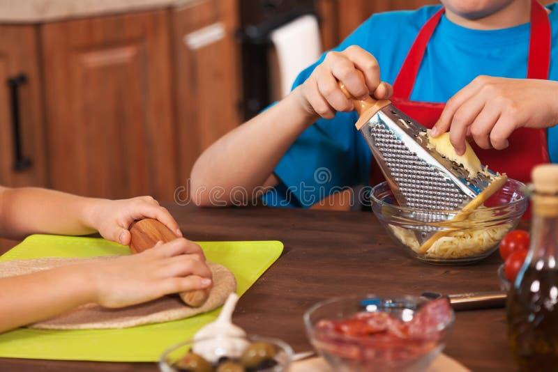 Enfants préparant un plan rapproché de pizza ensemble - sur des mains, département peu profond images libres de droits