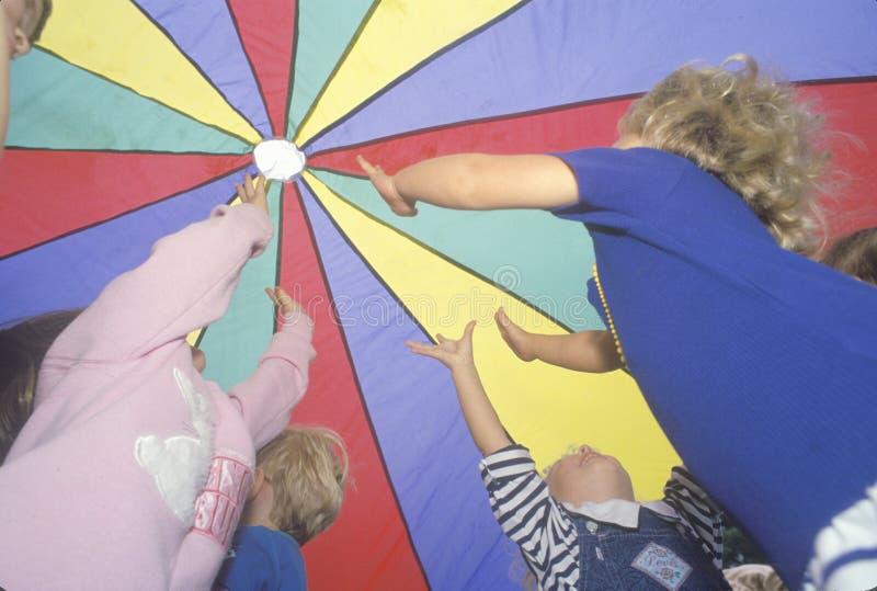 Enfants préscolaires jouant un jeu de parachute, Washington D C photographie stock libre de droits