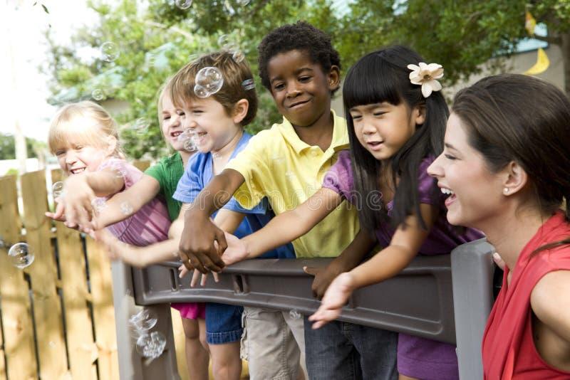 Enfants préscolaires sur la cour de jeu avec le professeur images stock