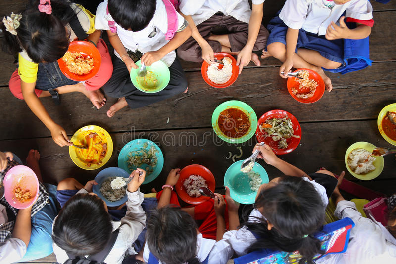 Enfants prenant le déjeuner à l'école asiatique image stock