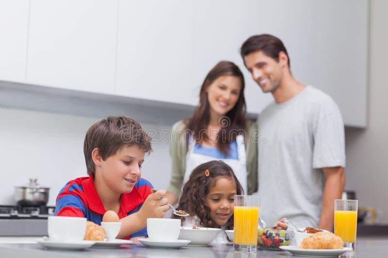 Enfants prenant le petit déjeuner dans la cuisine images libres de droits