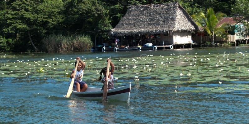 Enfants ramant dans un petit bateau. images stock