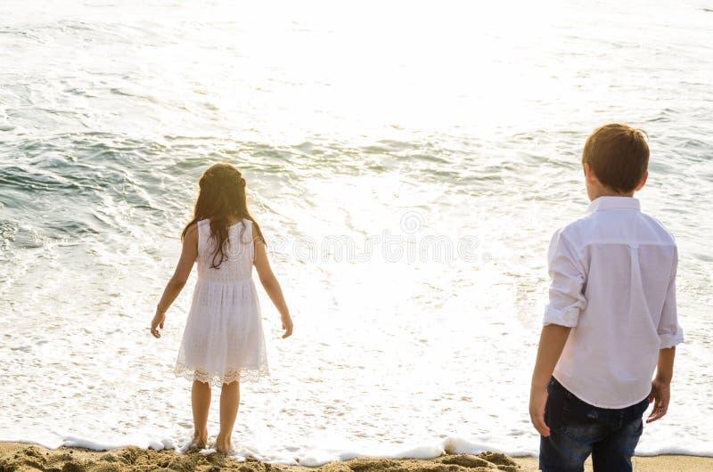 Enfants regardant la mer avec le sien de nouveau à la caméra photo libre de droits
