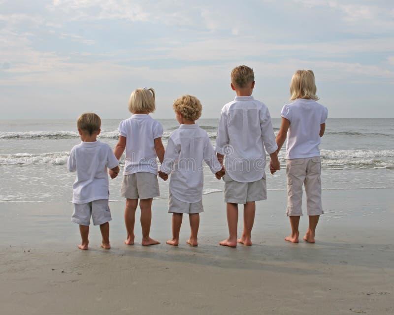 Enfants retenant des mains à la plage photographie stock libre de droits