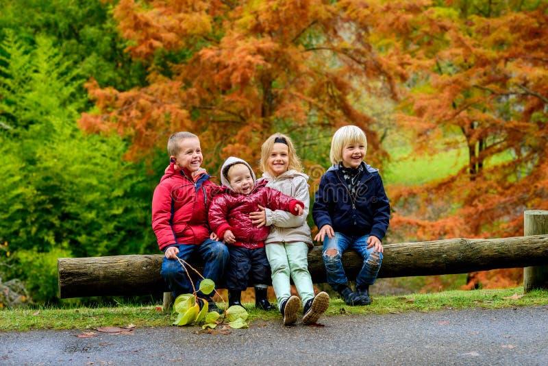 Enfants riants s'asseyant ensemble photo stock