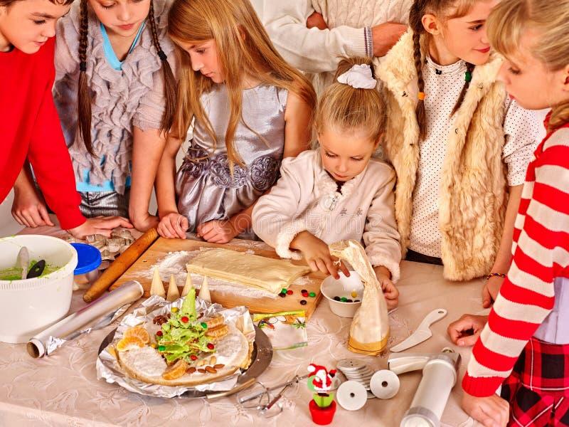 Enfants roulant la pâte dans la cuisine image stock