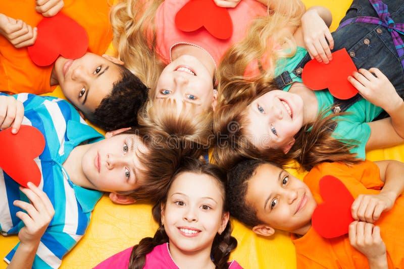 Enfants s'étendant en cercle avec des coeurs dans des leurs mains image libre de droits