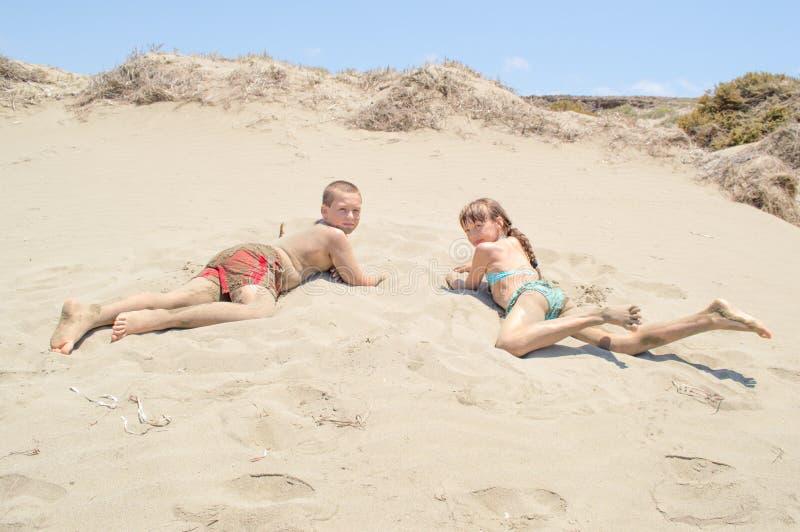 Enfants s'étendant sur le sable chaud images libres de droits