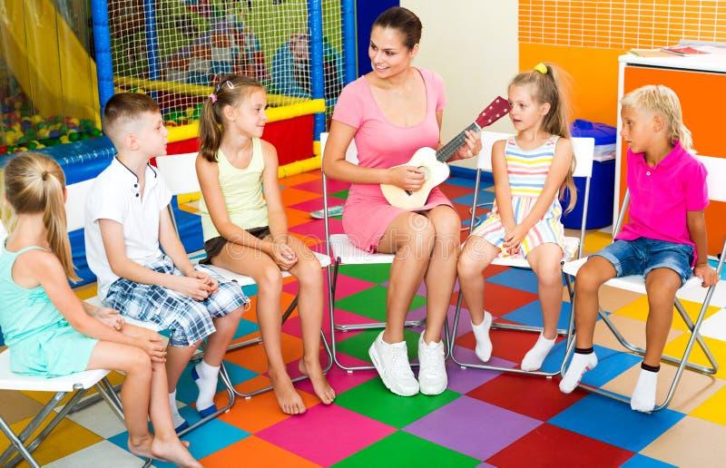 Enfants s'asseyant autour du professeur avec la petite guitare photographie stock