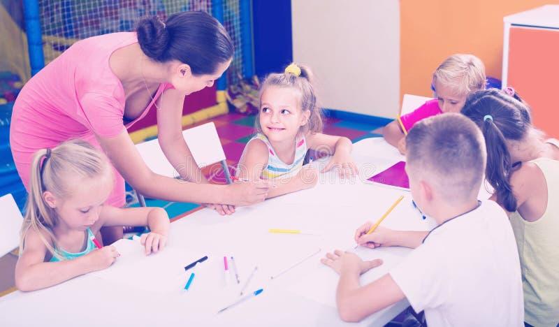 Enfants s'asseyant ensemble et dessinant dans la classe à l'école photo libre de droits