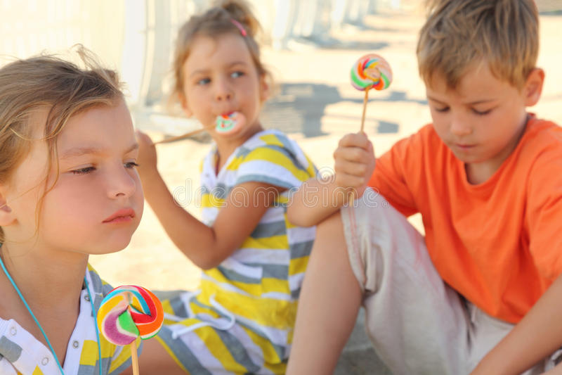 Enfants s'asseyant sur la plage et mangeant des lucettes photographie stock