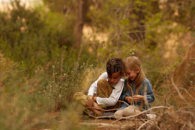 Enfants s'asseyant sur la terre en nature images libres de droits