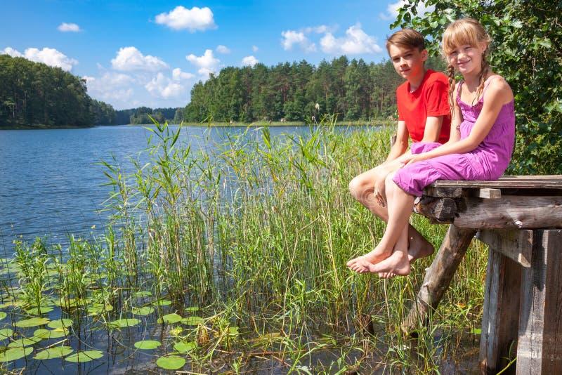 Enfants s'asseyant sur un pilier par un lac d'été images stock
