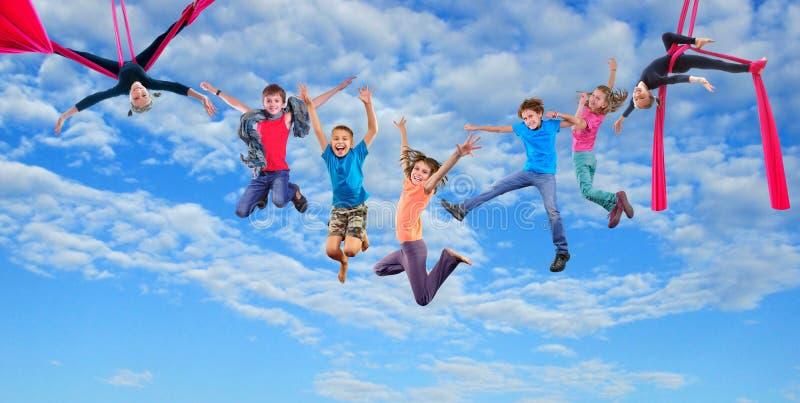 Enfants sautants de danse heureuse en ciel image libre de droits