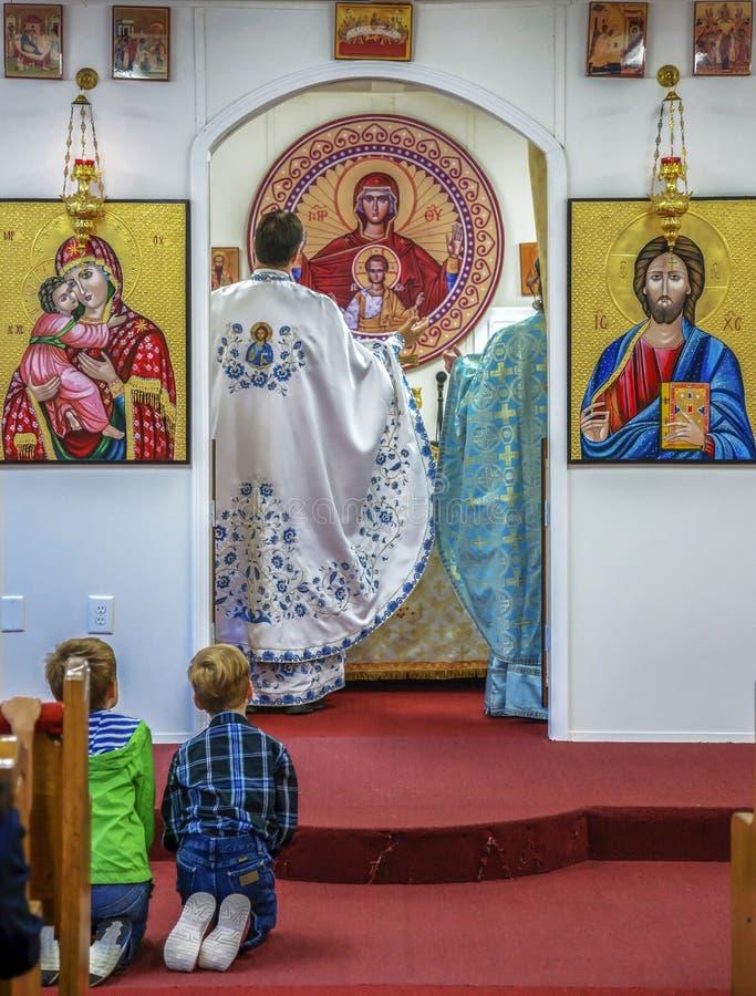 Enfants se mettant à genoux devant l'autel et la prière image libre de droits