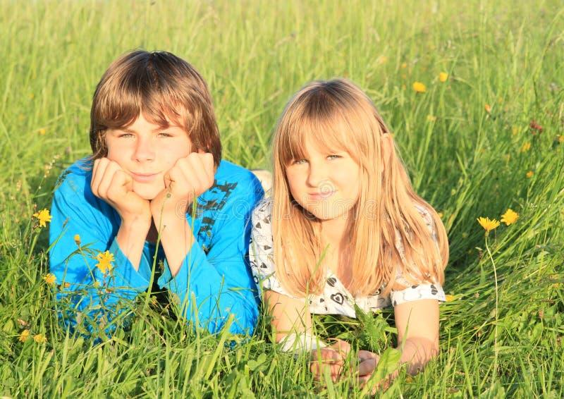 Enfants se situant dans l'herbe photographie stock