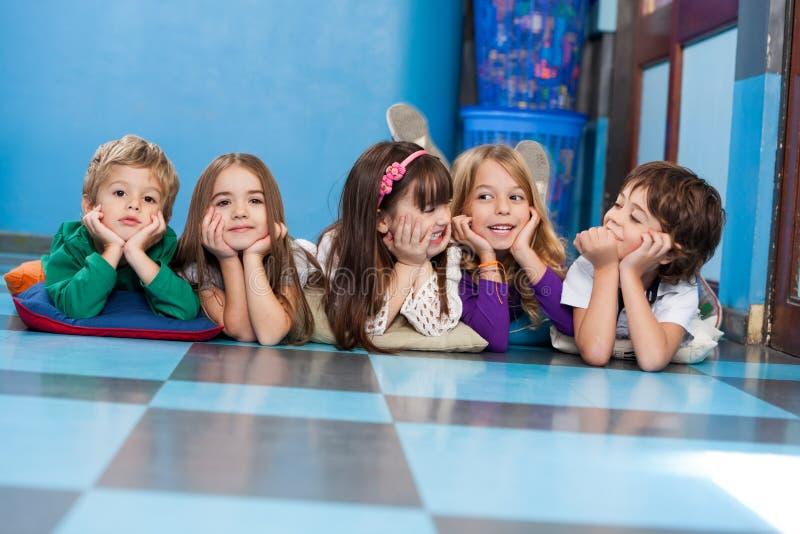 Enfants se situant dans une rangée sur le plancher photos stock