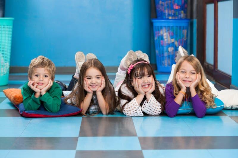 Enfants se situant dans une rangée sur le plancher dans la salle de classe photographie stock libre de droits