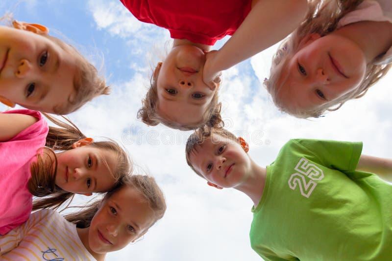 Enfants se tenant se penchants regardant la caméra photographie stock