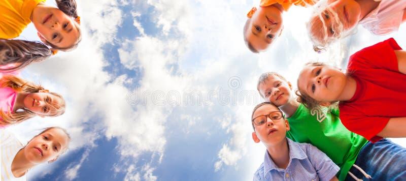 Enfants se tenant se penchants regardant la caméra image stock