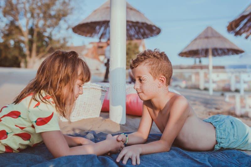 Enfants se trouvant sur la plage et tenant des mains photos stock