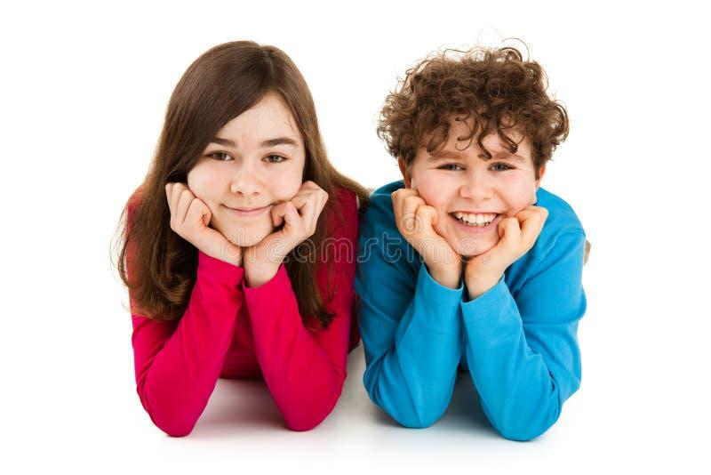 Enfants se trouvant sur le fond blanc image stock
