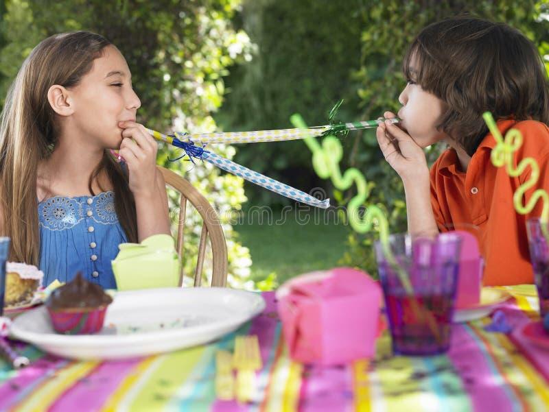 Enfants soufflant des décolleurs de partie à la fête d'anniversaire photo libre de droits