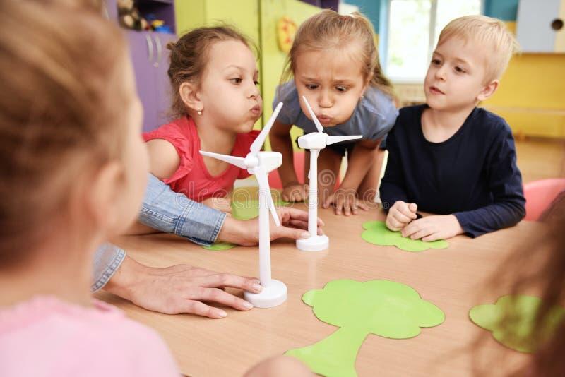 Enfants soufflant le modèle de la turbine de vent images stock