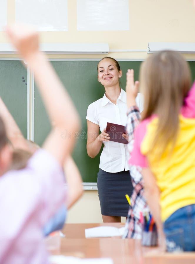Enfants soulevant des mains connaissant la réponse à la question photos stock