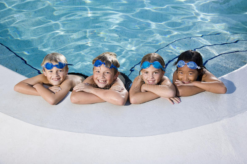 Enfants souriant au bord de la piscine photographie stock