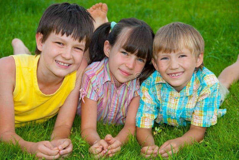 Enfants sur l'herbe verte image stock