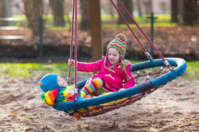 Download Enfants Sur L'oscillation De Terrain De Jeu Photo stock - Image du kindergarten, frère: 77150508