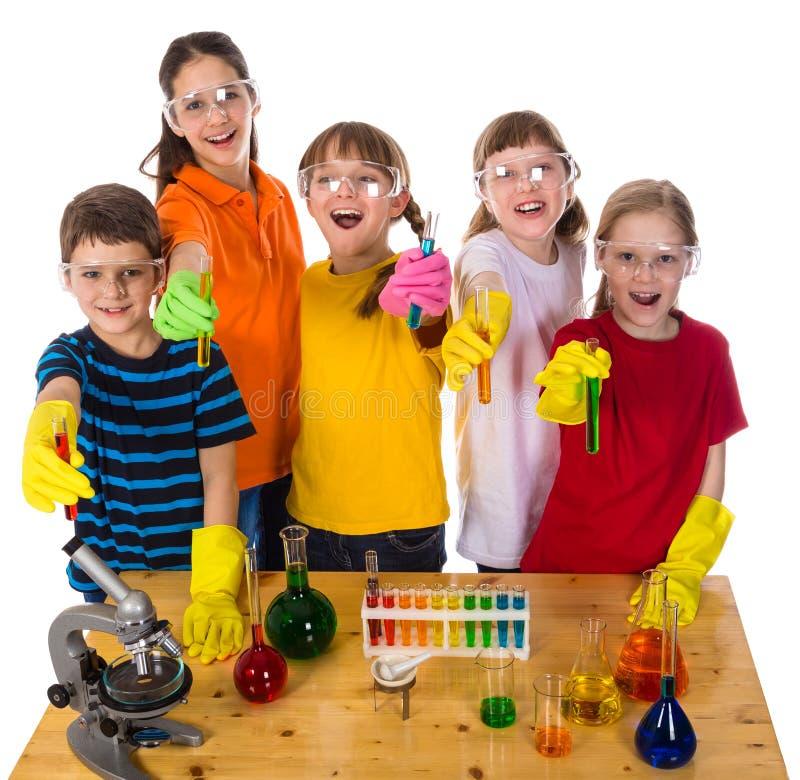 Enfants sur la table tenant les essai-tubes chimiques photographie stock